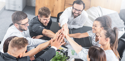 Business people happy showing team work and giving five in office