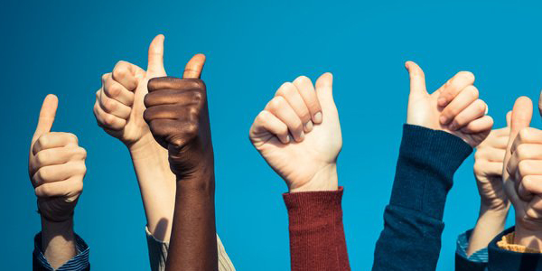 A group of people give thumbs up